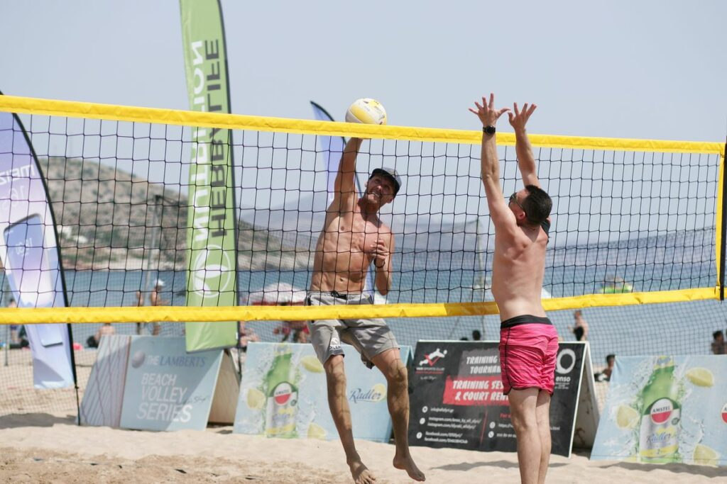 Men playing beach volleyball in Athens