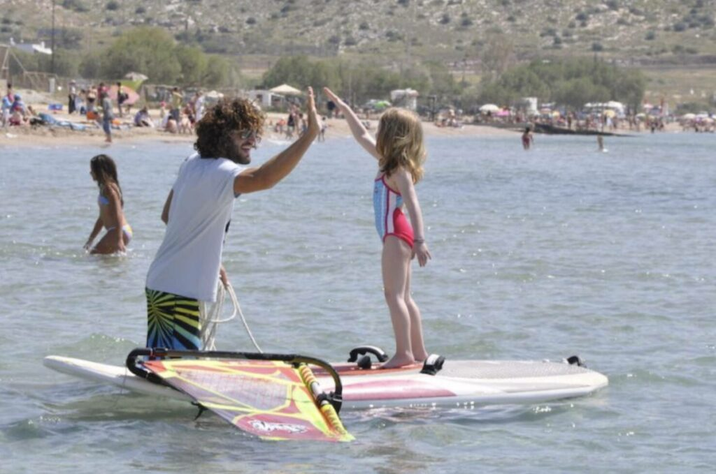 Windsurf instructor high fiving little girl on windsurf board